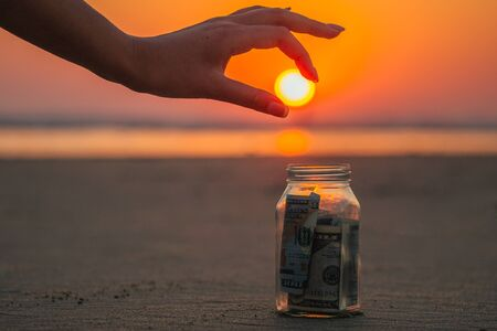 a glass jar with coins and bills on the beach against the sunset. the concept of accumulation of money for travel Stock fotó