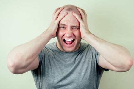 a portrait of a bald man is sad against a gray background. problem of male pattern baldness. sadness, vexation and anger