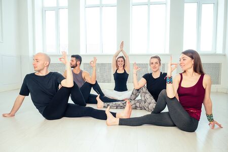 a happy group of people from men and women practicing yoga in the studio. groups of meditation and communication yoga class. the concept of group meditation and teamwork. the concept of anti-stress Stock Photo