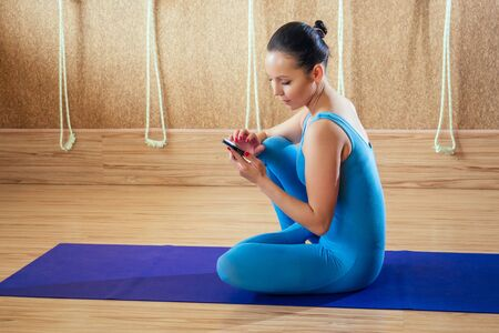 A young and beautiful woman is sitting in a lotus pose and is holding a phone. The concept of concentration, stretching and yoga practice