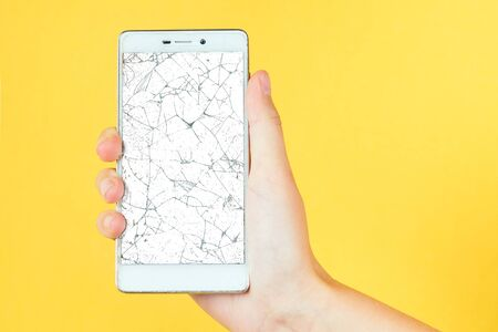 hand on a yellow background holding a phone with a broken screen