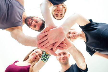 a happy group of people from men and women practicing yoga in the studio. groups of meditation , communication yoga class. the concept of group meditation and teamwork. coach and students in a circle Stock Photo
