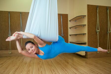 portrait of a beautiful young woman engaged in anti-gravity yoga on canvases. yoga on the hammock. The concept of aero-yoga and the development of flexibility and stretching