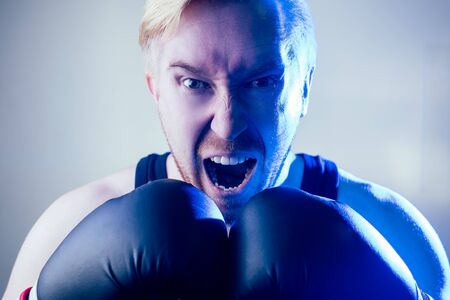 a portrait of a furious and evil male boxer doing sports in the gym. boxer and boxing gloves on a dark background. the man strikes. bandage on the hands Stock Photo