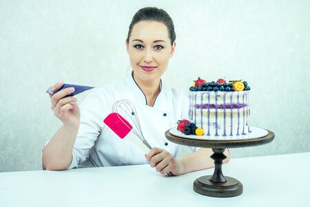 beautiful and smiling woman confectioner in white work uniform adorns the cake in the kitchen. confectioner, cake, cooking. wedding and birthday cake with berries