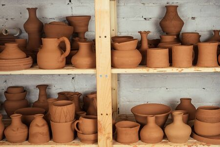 A shelf with vases and pots of clay. potter, clay, vase, pottery and potter. shelves with brown pottery 版權商用圖片