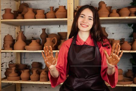A beautiful potter girl works with clay and makes a pot of mastre. a woman works with clay on a potters wheel. potter shows his hands stained with clay Imagens - 132066747