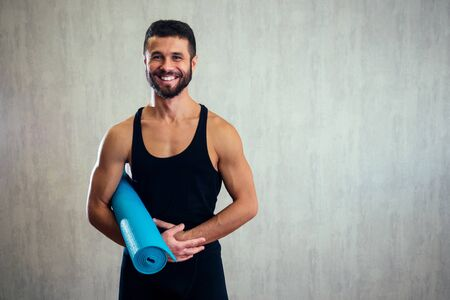handsome man holding a yoga mat on the floor. blue yoga mat and stretching instructor Stock Photo
