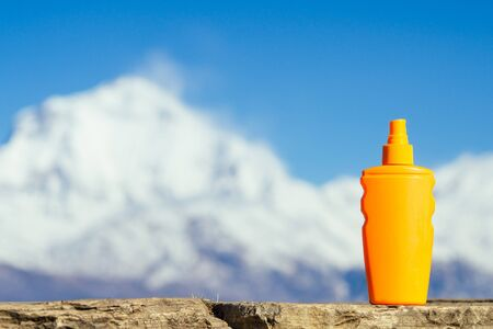 sunscreen in an orange bottle on a mountain background. the concept of preventing skin cancer and the use of sunscreen in the mountains.