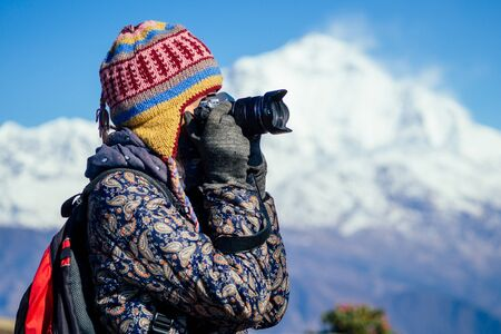 a young tourist woman with a hiking backpack and a knitted hat photographing landscapes in the Himalaya Mountains. trekking concept in the mountains 写真素材