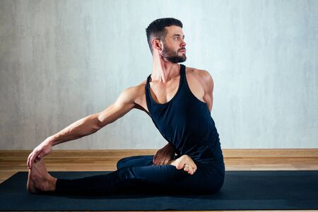 a man in dark sports clothes practicing yoga in a lotus position on a gray background. asana on the floor on yoga mats. the concept of concentration and possession of the body Imagens - 132066758