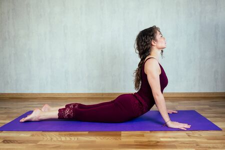 happy beautiful woman with curly hair practicing yoga on a yoga mat on a gray wall background. concept of health practice, yoga and stretching