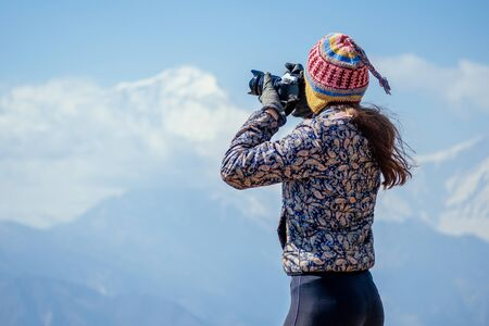 a young tourist woman with a hiking backpack and a knitted hat photographing landscapes in the Himalaya Mountains. trekking concept in the mountains Stock Photo