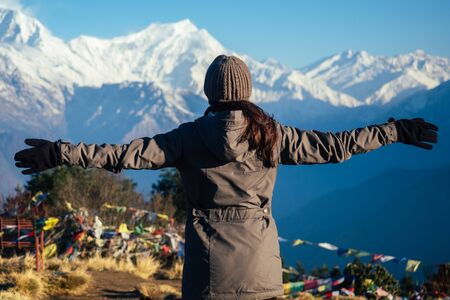 a young tourist woman with a hiking backpack and a knitted hat in the Himalaya mountains. trekking concept in the mountains