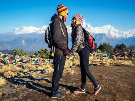 A beautiful and active woman and a man are hugging against the background of the mountains. the concept of active recreation and tourism in the mountains. couple in love trekking in Nepal Himalayas