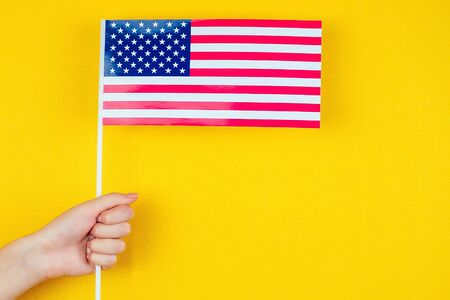 Female hand holding an American flag on a yellow background. Concept of the Independence Day of America July 4