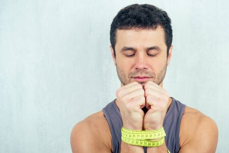portrait of a young beautiful brunette man with bound measuring tape hands. concept of diet and healthy eating