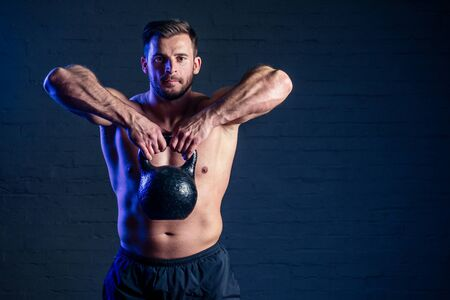 young and handsome man athlete doing exercise for the muscles of the body with weights dumbbell in the gym