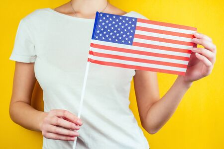 American flag in female hands with a white t-shirt on a yellow background. Concept of the Independence Day of America July 4