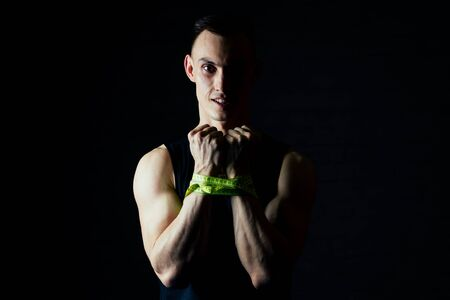 portrait young man measures his hand with a measuring tape in the gym on a dark background
