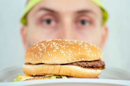 portrait of a young handsome bald hunger man with a measuring tape looking at a high-calorie big burger on a plate. concept of diet, unhealthy and healthy eating