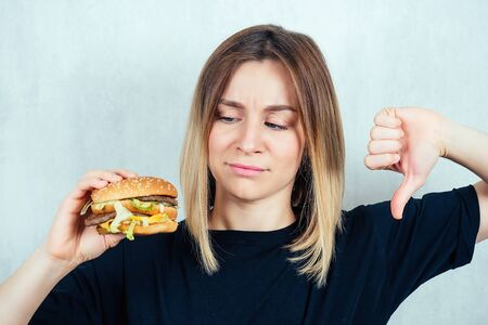 young and attractive blond woman in black T-shirt and measuring tape holding a high-calorie burger and showing thumbs down. slimming and diet concept