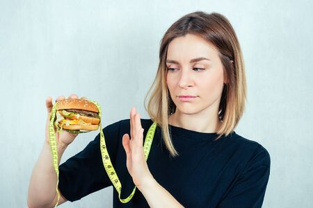 young and attractive blond woman in black T-shirt and measuring tape is holding a high-calorie burger and shows a hand gesture stop. concept of refusing harmful fast food and diet Stock Photo