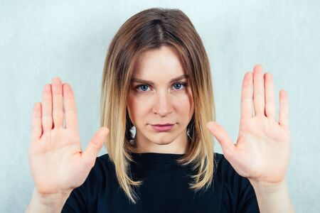 young and attractive blond woman in black t-shirt showing stop gesture.