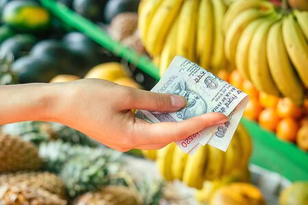 Indian rupees in the hands of women choose fruit in the market in Asia. concept of tourism and recreation Фото со стока