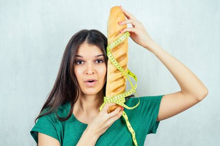 portrait of a hungry, young and beautiful brunette woman holding a high-calorie bun bread with a measuring tape. concept of diet and rejection of unhealthy harmful food Stock Photo