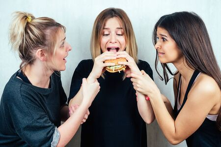 three friends persuade the girl not to eat a burger. concept of diet and female friendship. Stock Photo