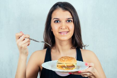 young and attractive sad woman in black T-shirt and measuring tape is holding a calorie burger on a plate. concept of rejection of harmful fast food and diet Stock Photo