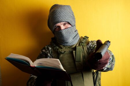 a terrorist man in a camouflage and a mask is holding a red book and weapons on a yellow background. the concept of anonymity and terrorism..