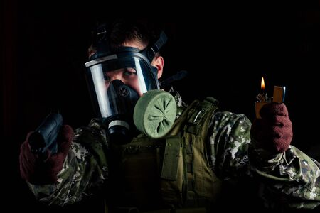 A terrorist man in a gas mask keeps a gun and a lighter on a black background. concept of mask threatens and wartime in a suit and gloves