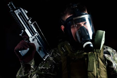 male terrorist in a gas mask holding a gun on a black background