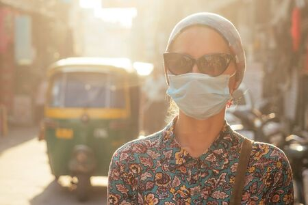 portrait of a young tourist woman wearing sunglasses and a mask on the background of a street with cars and people. the concept of tourism, health and safety in the Asian and Indian countries