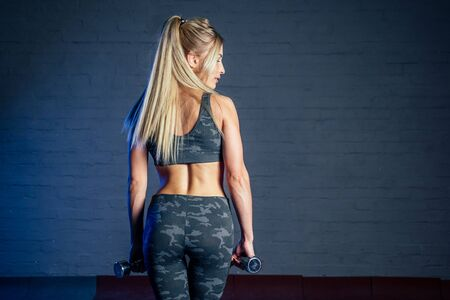 beautiful blond woman in a sexy camouflage sports suit is holding dumbbells in hands against a gray wall background view from the back