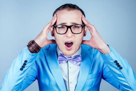 un uomo con gli occhiali e un abito elegante blu che gli tiene la testa. concetto di mal di testa, emicrania e stress
