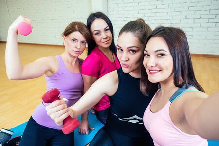 four beautiful and young women girlfriends are photographed selfie on the phone in sportswear in the gym. group portrait of a woman selfie having fun with dumbbells Banco de Imagens