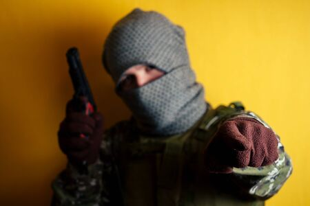 a man in a camouflage and a mask is holding a gun and pointing with his finger