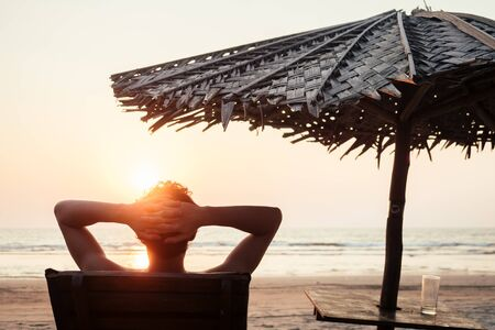 the man is resting on a sun lounger overlooking the sea and the sunset on the beach Reklamní fotografie