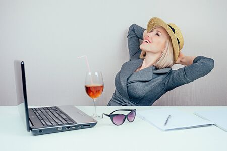 attractive female person business lady in stylish business suit and a straw hat dreams about vacation in office with cocktail and laptop on the table. travel concept and holiday