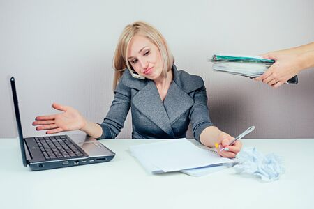 attractive smart blonde multitasking woman secretary business lady in stylish business suit working with laptop a bunch of folders and talking on the phone in office . business concept and deadline 스톡 콘텐츠