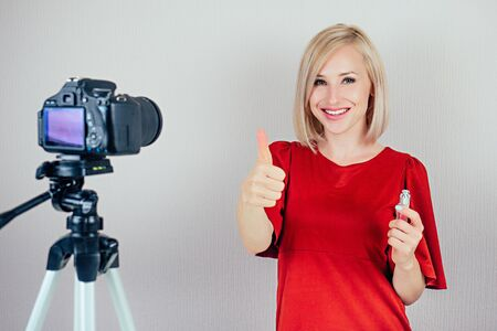 attractive blond videoblogger beauty blogger woman in a red dress records video blog about the care of the skin of the face and cosmetics on a video camera . concept of online makeup courses