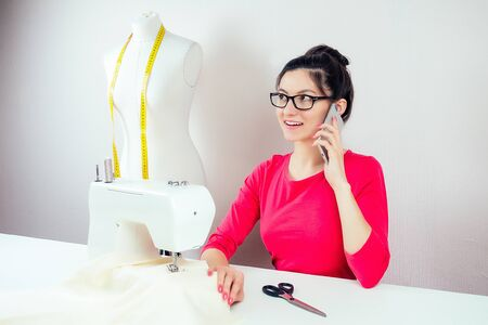 smiling girl seamstress with glasses talking on the phone about a sewing machine and a mannequin with a yellow measuring tape on a white background