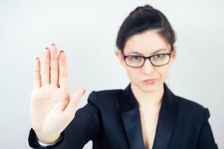 portrait of attractive strict brunette woman business lady in stylish business suit and glasses shows a hand gesture stop in the workplace office 스톡 콘텐츠