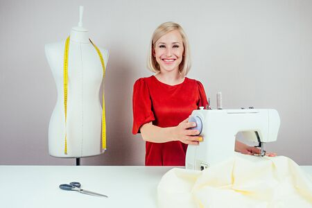 smiling girl seamstress working on sewing machine and mannequin with yellow measuring tape on white background