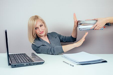 attractive smart blonde multitasking woman business lady in stylish business suit working with laptop and a bunch of folders angry and furious in panic in office . business concept and deadline