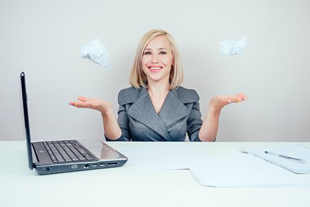 attractive smart blonde multitasking woman business lady in stylish business suit throws lumps of paper draft and having fun in office . business concept and deadline Banco de Imagens