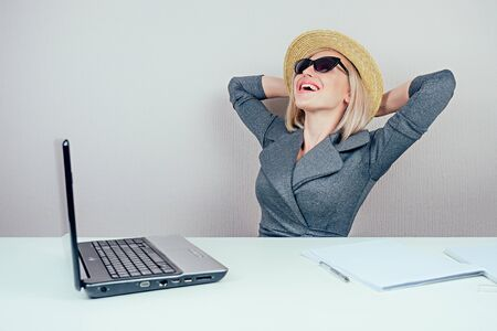 attractive woman blonde business lady in stylish business suit , in sunglasses and a straw hat dreams about vacation and sunbathing in office with laptop on the table. travel concept and holiday